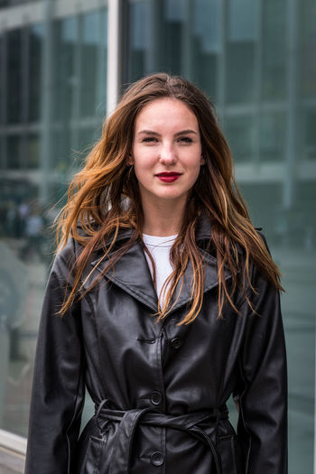 Portrait of young woman wearing a trench coat in city One Person Looking At Camera Beautiful Woman Trench Coat Fashion Beauty Lipstick Attractive Woman Urban Caucasian Young Adult Outdoors Day Autumn Brown Hair Front View Focus On Foreground Brunette Waist Up Long Hair