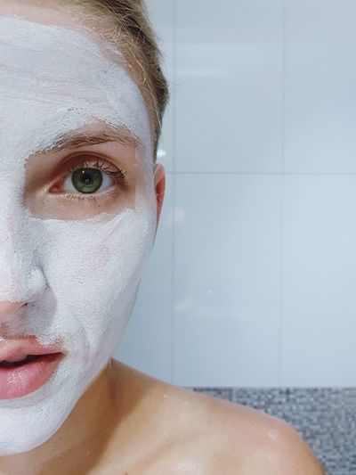 Close-up portrait of woman with facial mask in bathroom