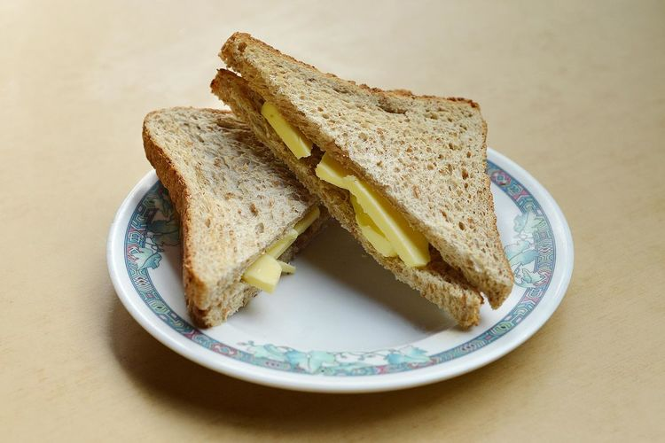 Close-Up Of Butter Slices In Bread On Plate