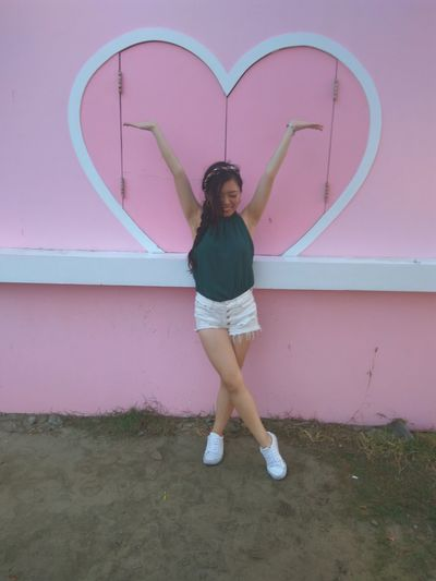 Woman with arms raised standing against heart shape on pink wall