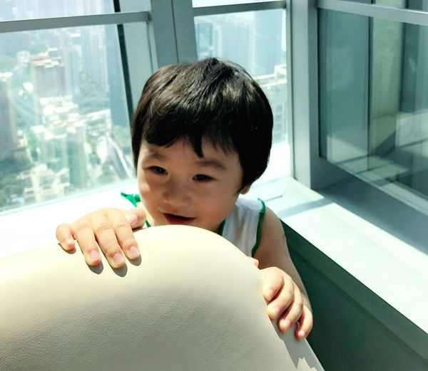 Cute baby boy playing by window at home