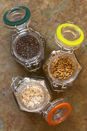 Chia seeds, toasted oat grains and oat flakes in swing top glass jars, photographed overhead on slate with natural light (Selective Focus, Focus on the top of the chia and oats) Breakfast Chia Cooking Raw Salvia Hispanica Seed Snack Baking Brunch Crunchy Fiber Food Food And Drink Grain Healthy Healthy Eating Ingredient Jar Oat Oat Flake Oatmeal Oats Overhead View Raw Food Roasted