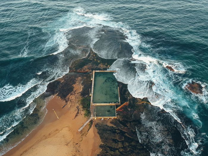Aerial view of waves breaking on rocks