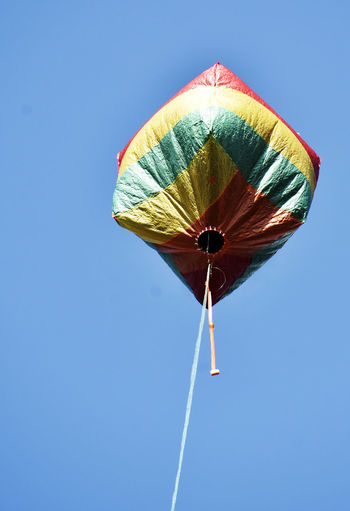 Low angle view of balloon against clear blue sky