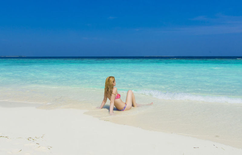 Young woman sitting on beach against sky