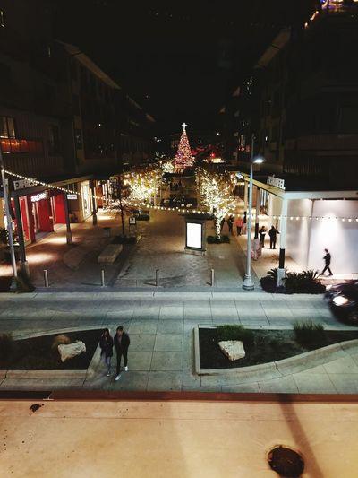 People on wet illuminated city at night