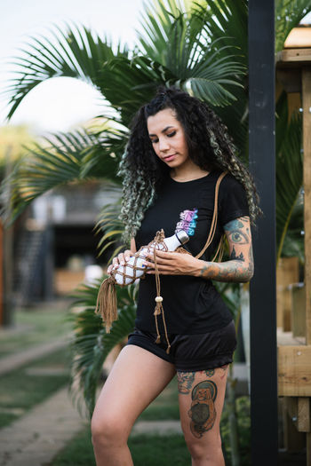 Young woman holding palm tree