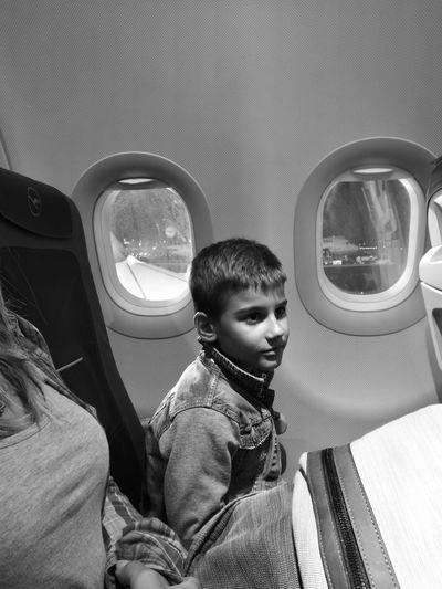 Boy sitting by window in airplane