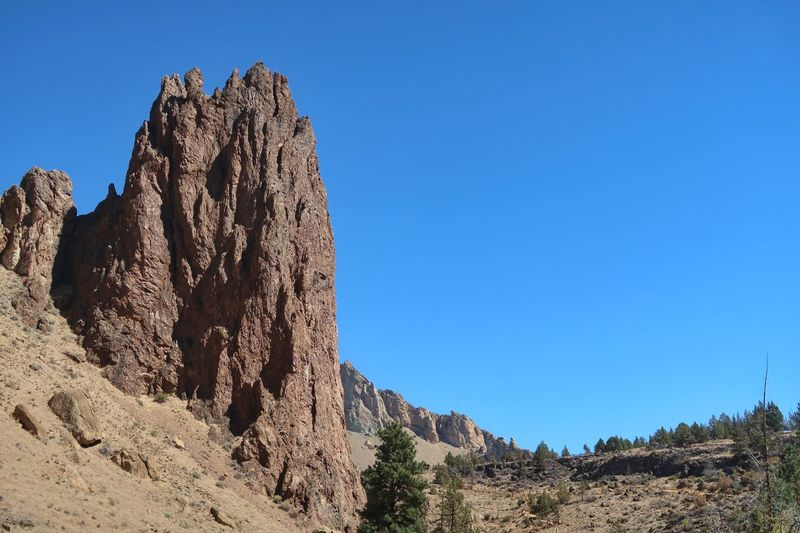 Low angle landscape of vertical rock formations in Smith Rock State Park in Oregon Rock Climbing Area Smith Rock State Park Oregon Barren Hills Blue Sky Travel Destinations Sky Blue Nature Clear Sky Copy Space Sunlight No People Tranquility Day Plant Low Angle View Solid Rock Formation Scenics - Nature Tranquil Scene Rock Beauty In Nature Outdoors Land