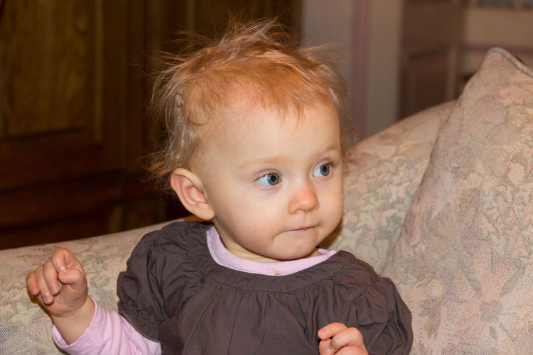 Cute baby girl looking away while sitting at home