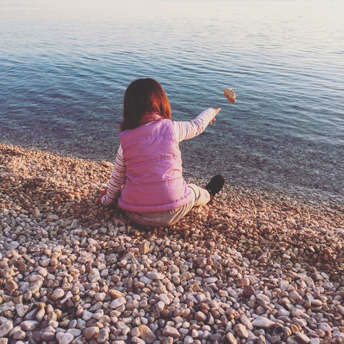 Rear View Of Playful Girl Throwing Stone In Sea While Sitting At Shore
