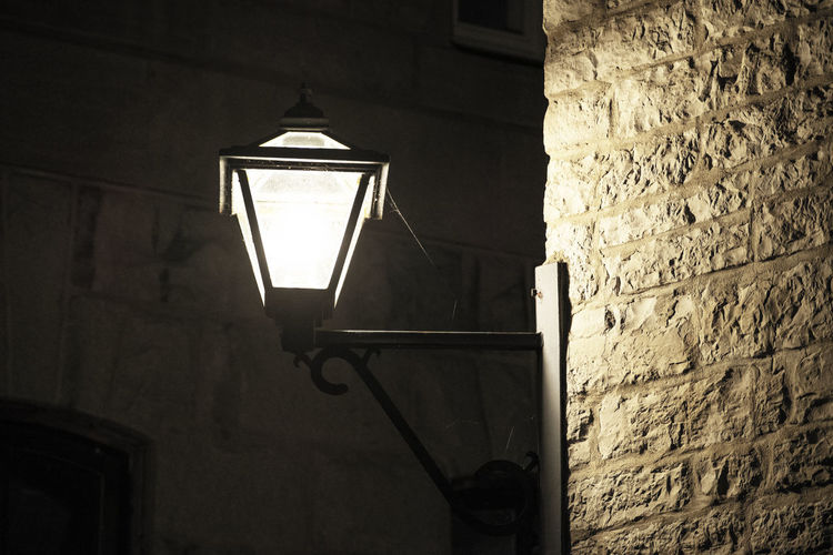 Low angle view of illuminated street light against wall
