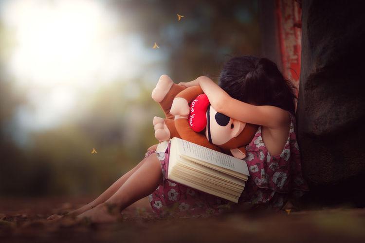 Cute girl sitting on book