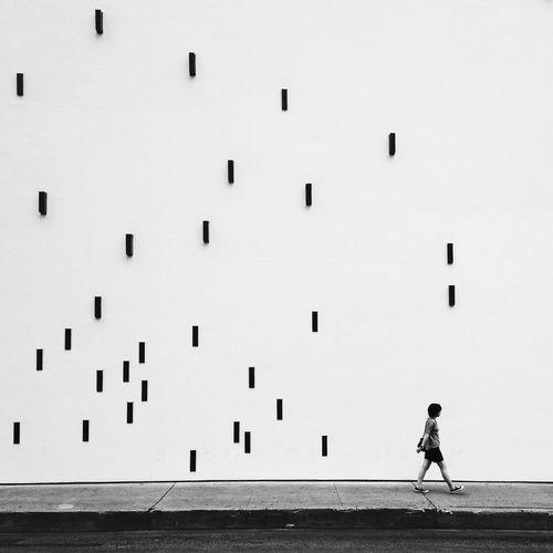 Man walking on sidewalk by artistic wall