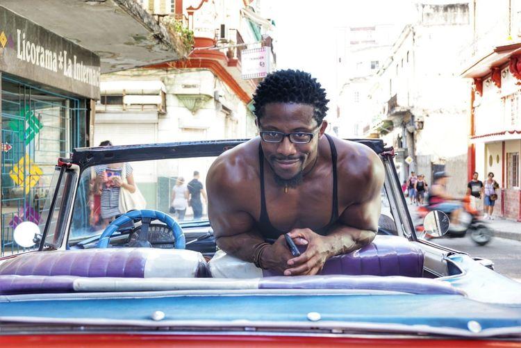 Portrait Of Man In Vintage Car On Street