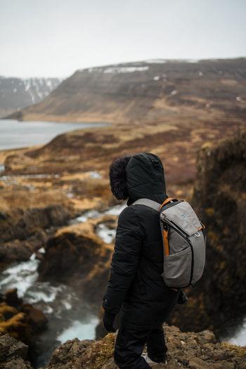 Full length of hiker standing on cliff against sky