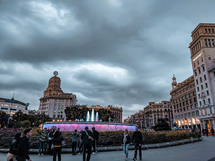 a fountain in Barcelona Fountain Lit Twilight Evening Square Barcelona Pink Light People Incidental People City Sky Architecture Cloud - Sky Storm Cloud Historic Dramatic Sky Overcast Storm Atmospheric Mood Cloudscape Moody Sky Cumulonimbus