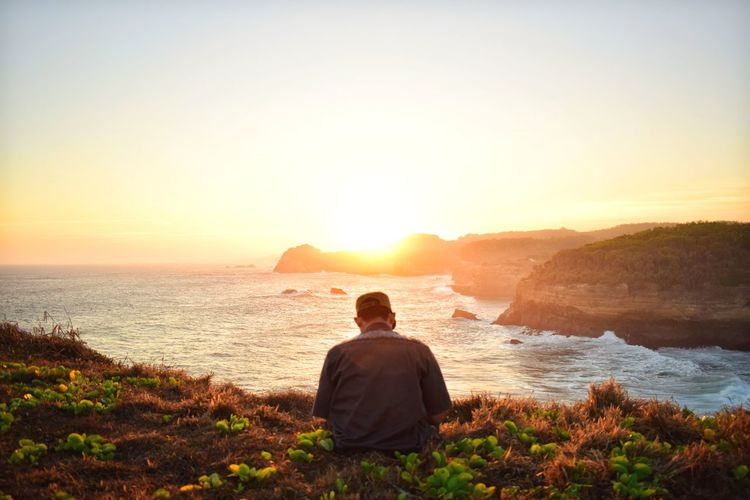 Rear view of man sitting on beach during sunset