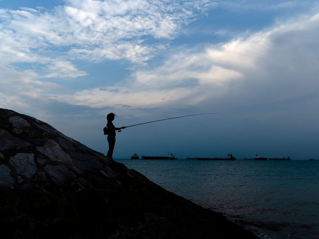 Girl fishing in late evening Sky Cloud - Sky Water Sea Real People Rock One Person Leisure Activity Lifestyles Activity Silhouette Outdoors Fishing Fishing Pole Lady Girl Females Fisherman Groyne Groin Early Morning