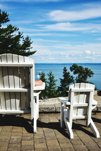 Chairs and table by sea against sky