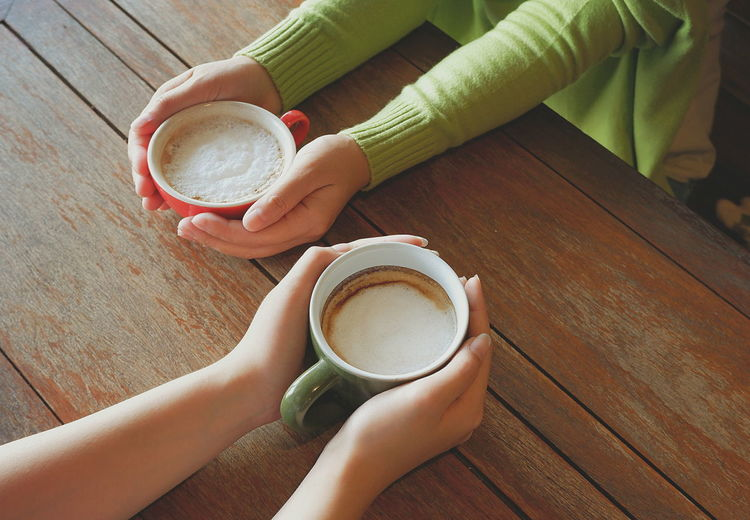 Two female playmate hands holding cups of cappuccino coffee on wooden tabletop in vintage tone style, high angle view with copy space Coffee Caffeine Friends Cup Frothy Buddy Playmate Long Sleeve Green Young Wooden Table Holding Diagonal Space Sunshine High Angle View Close Up EyeEm Selects Human Hand Cappuccino Frothy Drink Drink Women Holding Hot Drink Beverage Froth