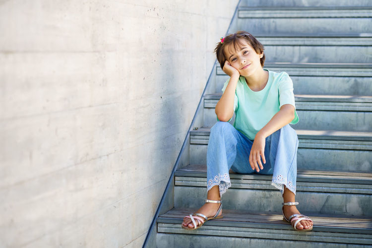 Full length of smiling girl sitting on staircase against wall