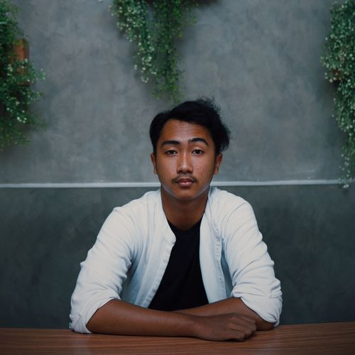 Portrait of young man sitting on table