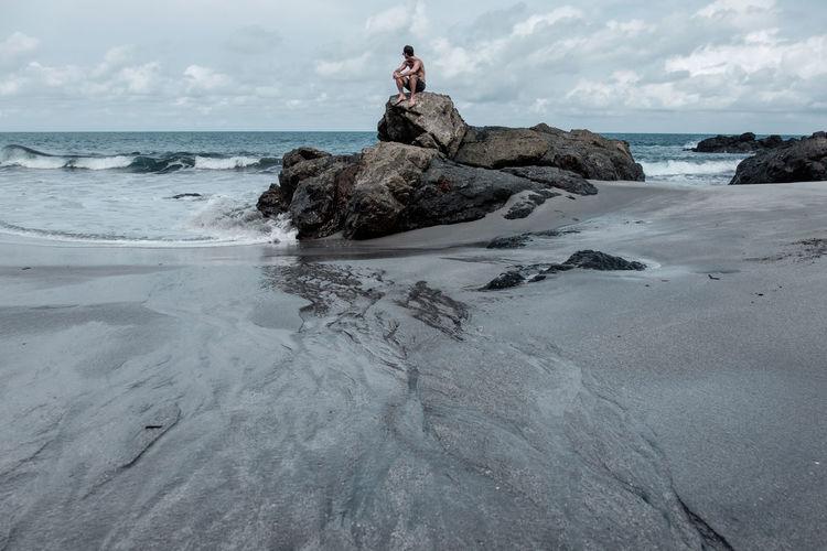 Man sitting on rocks at calm beach