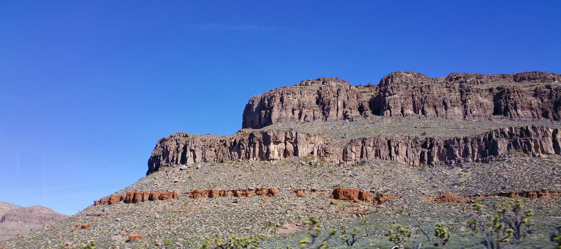 View of rock formation against clear blue sky, in the mojave desert