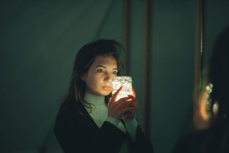 Young woman holding illuminated lighting equipment reflecting on mirror in darkroom