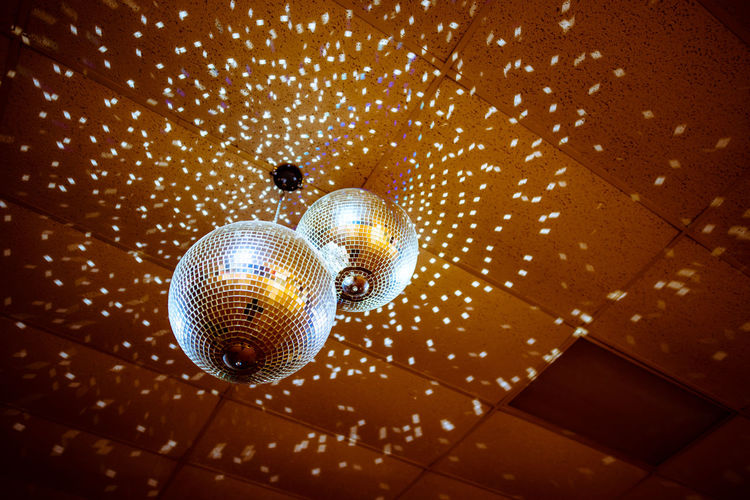 Low angle view of illuminated disco balls hanging from ceiling in nightclub
