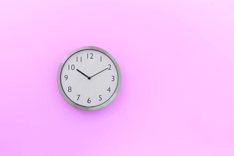 Close-Up Of Clock Against Pink Background