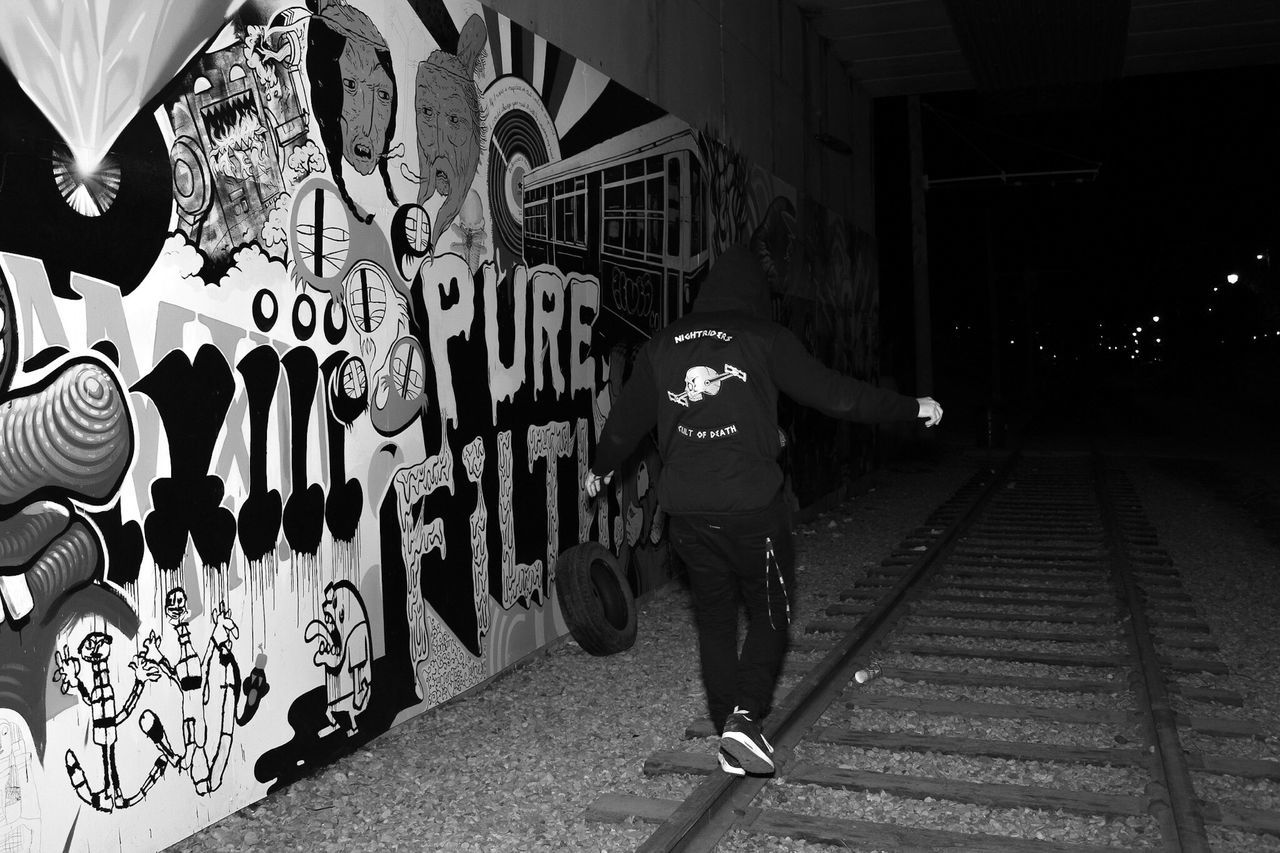 full length, real people, graffiti, walking, one person, night, men, lifestyles, outdoors, built structure, architecture, illuminated, city, building exterior, adult, people