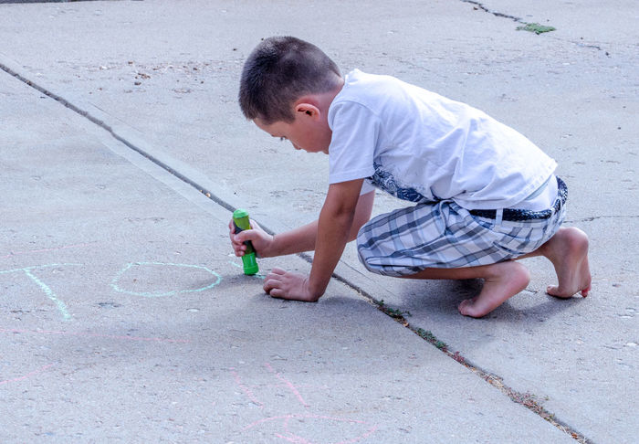 creativity need no boarders and paper cannot contains some ideas. this little boy needs a whole drive way for his artKids Summertime Active Kids Art Boys Childhood Creative Day Drawing Kids Having Fun One Person Outdoors People Playing Outdoors Real People Sidewalk Chalk
