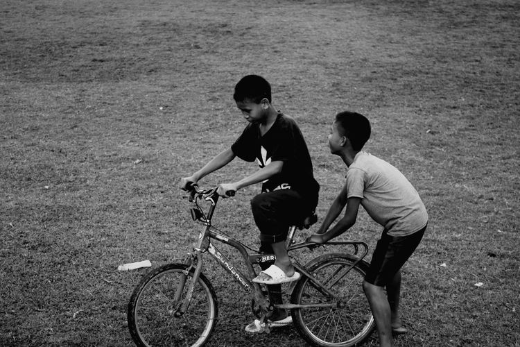 Teenage boys riding bicycle on field