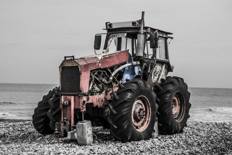 Tractor on field by sea against sky
