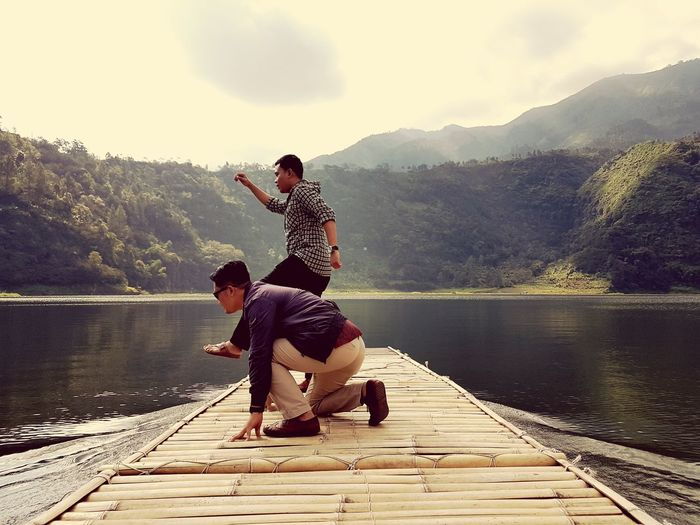 Male friends on wooden raft at lake