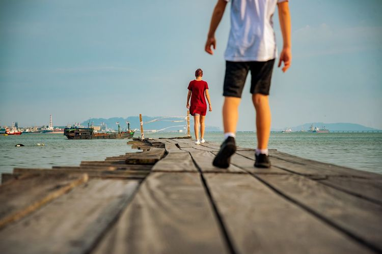 Rear view of people standing on pier by sea against sky