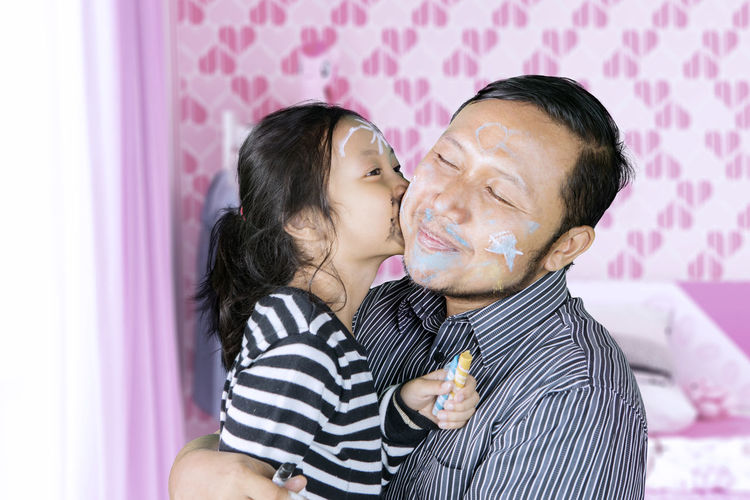 Daughter Kissing On Father Cheek With Drawn Face At Home