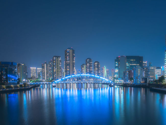 The river and skyscrapers of metropolis. Architecture Blue Building Exterior Built Structure Business City City Life Cityscape Clear Sky Corporate Business Development Downtown District Financial District  Futuristic Illuminated Modern Night No People Outdoors Sky Skyscraper Travel Destinations Urban Skyline Waterfront