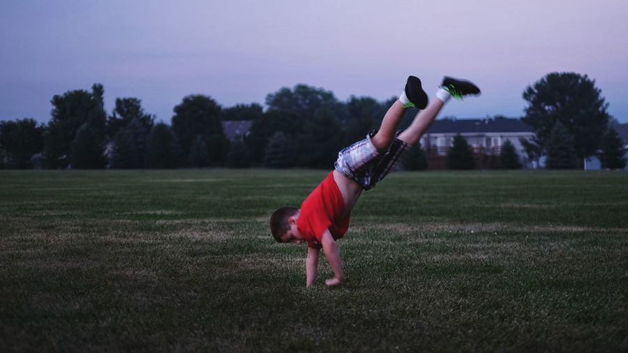 Full length of boy performing handstand on grassy field against sky