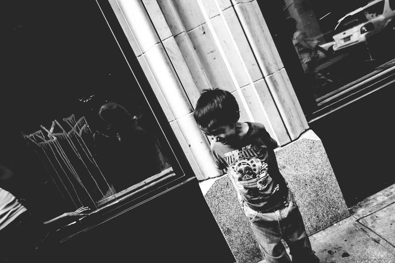 High angle view of boy standing by window