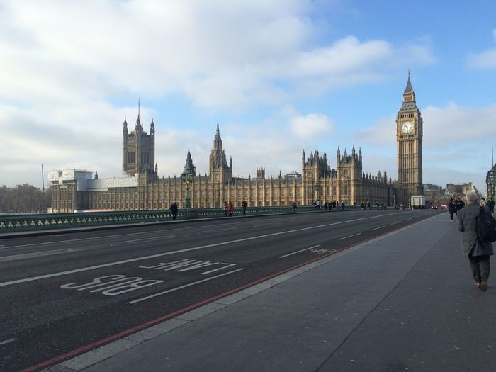 View Of Palace Of Westminster From City Street Against Cloudy Sky