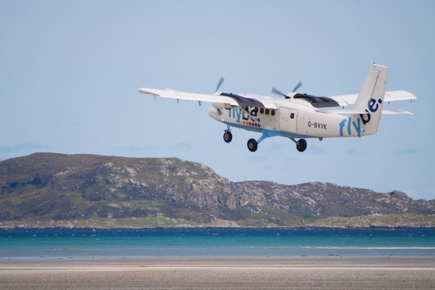 A flight takes off from the beach runway at Barra Airport, Scotland Beach Airport Take Off Flight Twin Otter Na H-eileanan Siar Hebrides Isle Of Barra Barra Airport Barra Loganair Flybe EyeEm Selects Sea Transportation Air Vehicle Day Airplane Mid-air Flying Sky Mountain Nature Outdoors Water No People