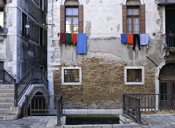 Typical old Venetian facade made of red bricks and cement with colorful clothes hanging outside the windows above a traditional canal with a dock for the gondola Façade Typical Venetian Architecture Bricks Bridge Building Canal Cement City Clothes Clothing Colorful Concrete Dock Italian Italy Laundry Nobody Old Traditional Veneto Venice Wall Window