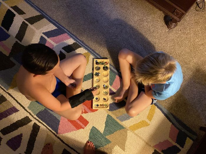 High angle view of siblings playing on floor