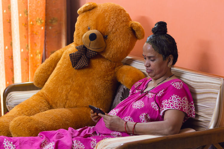 Senior lady with henna on her hair is smiling while watching her mobile phone indoors in isolation.