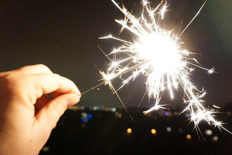 Cropped image of hand holding illuminated sparkler at night