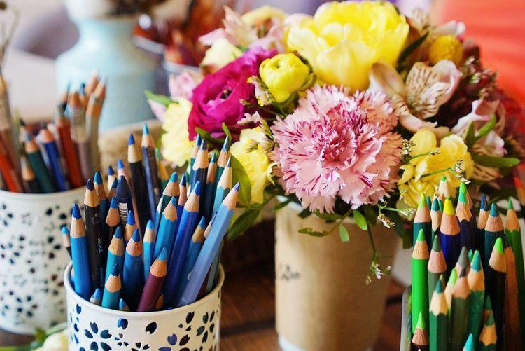 Close-up of colorful pencils by flowers