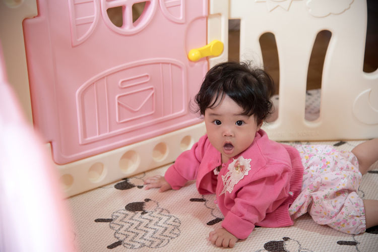 Portrait of cute girl in crib at home